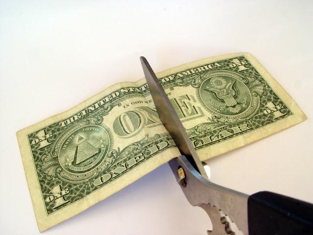 nůžky přestřihující bankovku